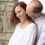 homme-embrasse-cou-de-sa-femme-couleur-couple-maries-en-blanc-maison-en-pierres-photographe-seance-couple-fiancailles-engagement-christelle-labrande-mariage-ales