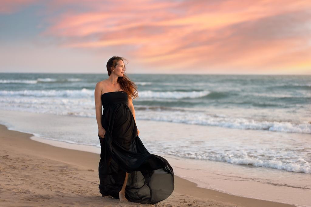 femme-robe-noire-enceinte-cheveux-longs--seance-photo-grossesse-avec-christelle-labrande-photographie-espiguette-beach-plage-grau-du-roi-coucher-de-soleil-sunset