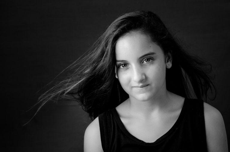 portrait-fille-ado-noir-et-blanc-cheveux-au-vent-sourire-christelle-labrande