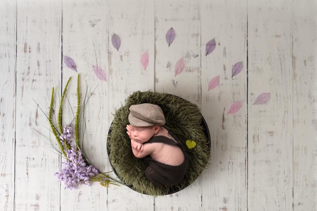 bébé-nouveau-né-photo-couleur-fleur-panier-plancher-blanc-béret-sur-fourrure-verte
