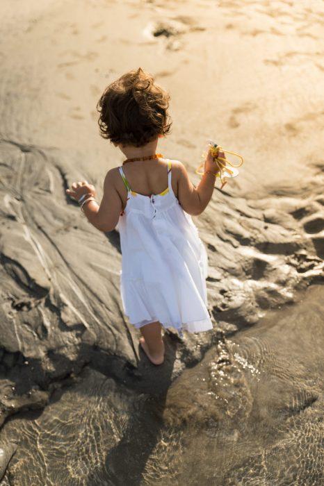 fille-robe-fraiche-de-dos-sable-plage-eau